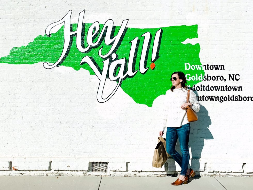 Eastern North Carolina Travel Guide: Top 10 Things to Do in Goldsboro NC by popular North Carolina blog, I'm Fixin' To: image of a woman standing next to a wall mural.