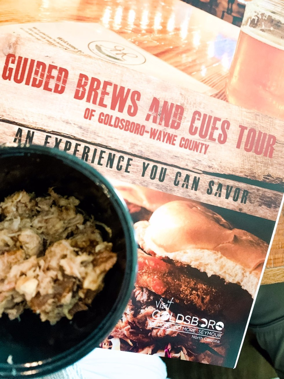 Eastern North Carolina Travel Guide: Top 10 Things to Do in Goldsboro NC by popular North Carolina blog, I'm Fixin' To: image of a Brews and Cues tour booklet.