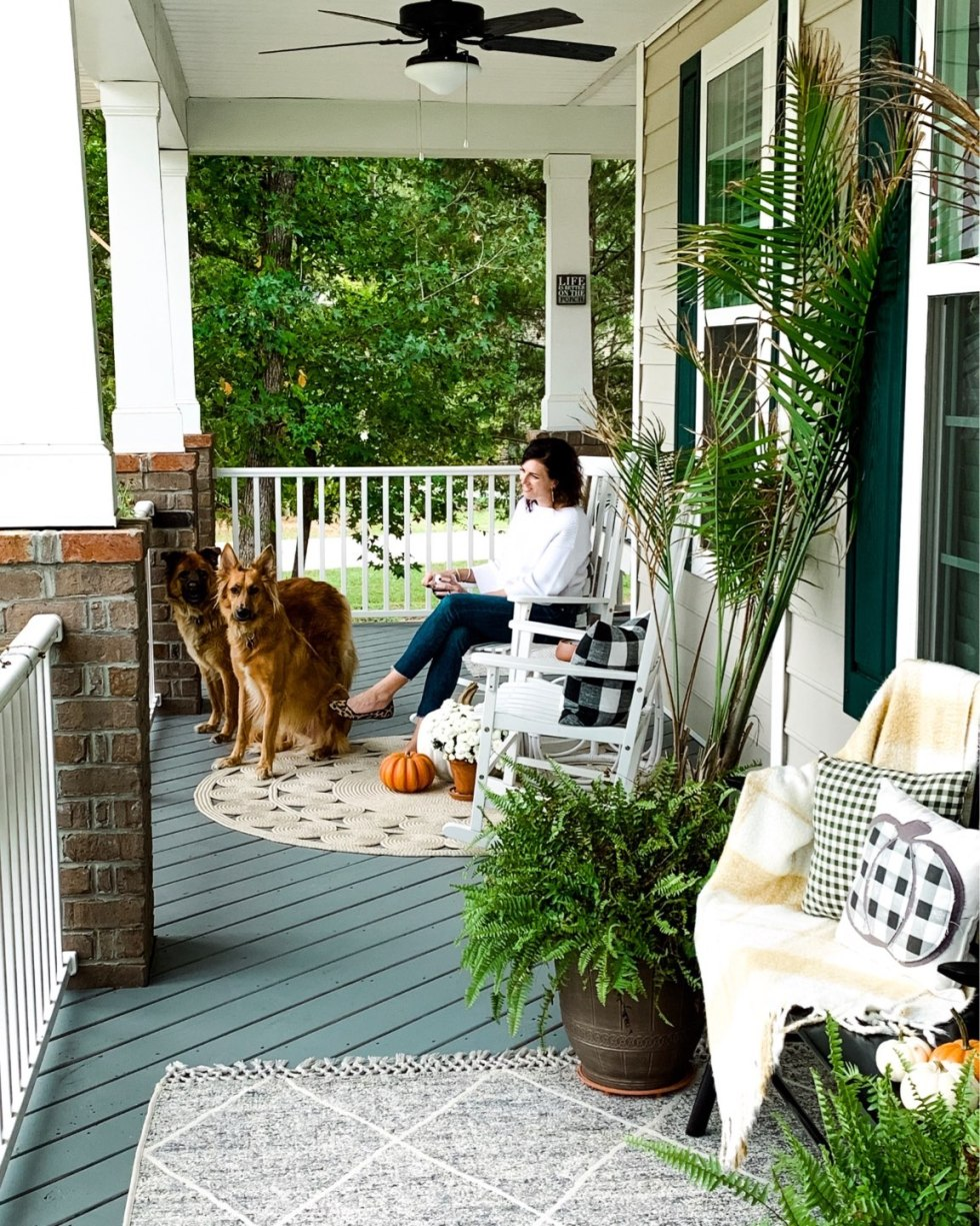 "Our Inviting and Cozy Fall Front Porch Decor Ideas - I'm Fixin' To - @mbg0112 | Our Inviting and Cozy Fall Front Porch Decor Ideas by popular North Carolina lifestyle blog, I'm Fixin' To: image of a woman and her two dogs sitting on a front porch decorated with a Target Opalhouse Desert Hatch Outdoor Rug Gray, Amazon Jerimiah Spindleback BenchAmazon 4TH Emotion Set of 2 Farmhouse Buffalo Check Plaid Throw Pillow Covers, Target Smith and Hacken 12"" Iron Galvanized Planters, Target Threshold 22"" Artificial Berry Wreath White, pumpkins, Target Smart Living San Rafael II 15"" LED Solar Mission Outdoor Lanterns, Hayneedle Coral Coast Indoor/Outdoor Mission Slat Rocking Chairs, mums, and green plants."