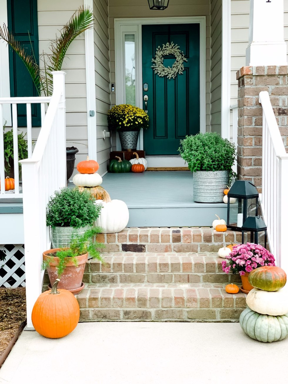 "Our Inviting and Cozy Fall Front Porch Decor Ideas - I'm Fixin' To - @mbg0112 | Our Inviting and Cozy Fall Front Porch Decor Ideas by popular North Carolina lifestyle blog, I'm Fixin' To: image of a front porch decorated with Target Smith and Hacken 12"" Iron Galvanized Planters, Target Threshold 22"" Artificial Berry Wreath White, pumpkins, Target Smart Living San Rafael II 15"" LED Solar Mission Outdoor Lanterns, mums, and green plants."