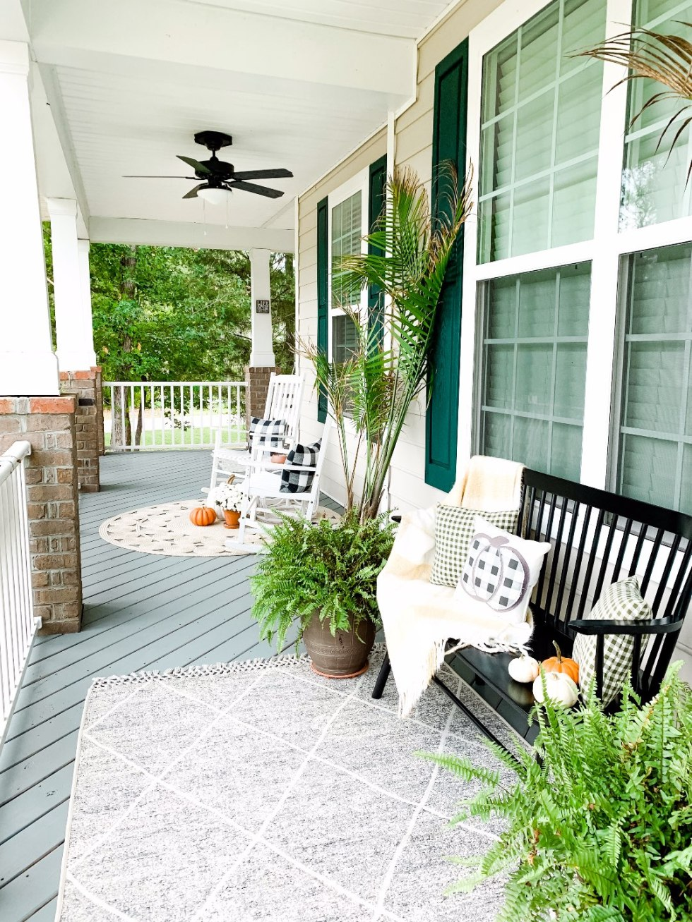 "Our Inviting and Cozy Fall Front Porch Decor Ideas - I'm Fixin' To - @mbg0112 | Our Inviting and Cozy Fall Front Porch Decor Ideas by popular North Carolina lifestyle blog, I'm Fixin' To: image of a front porch decorated with a Target Opalhouse Desert Hatch Outdoor Rug Gray, Amazon Jerimiah Spindleback BenchAmazon 4TH Emotion Set of 2 Farmhouse Buffalo Check Plaid Throw Pillow Covers, Target Smith and Hacken 12"" Iron Galvanized Planters, Target Threshold 22"" Artificial Berry Wreath White, pumpkins, Target Smart Living San Rafael II 15"" LED Solar Mission Outdoor Lanterns, Hayneedle Coral Coast Indoor/Outdoor Mission Slat Rocking Chairs, mums, and green plants."