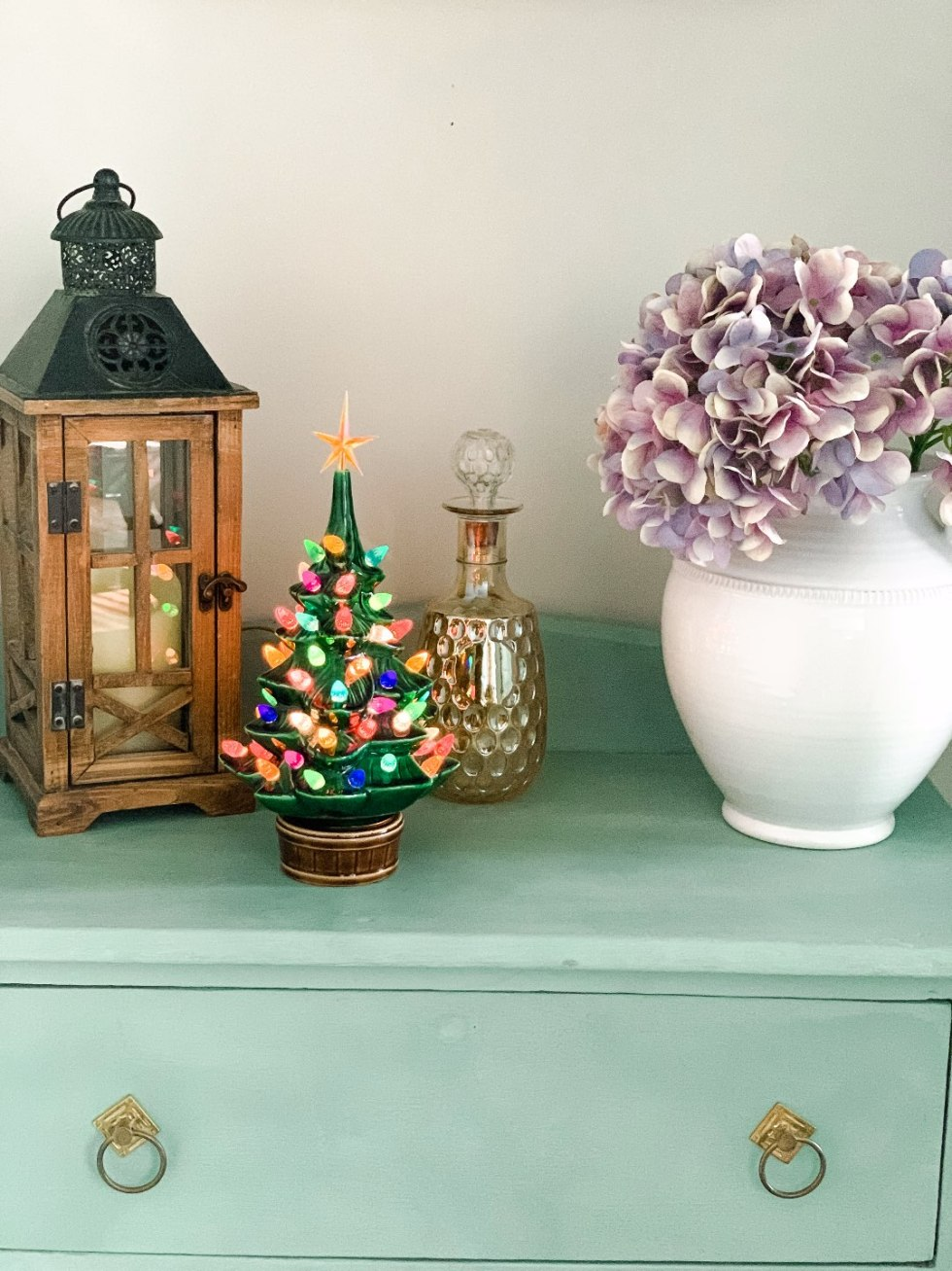 Holiday Home Decor Tour - I'm Fixin' To - @mbg0112 | Holiday Home Decor Tour by popular North Carolina life and style blog, I'm Fixin' To: image of a dresser with a glass light up Christmas tree on it.