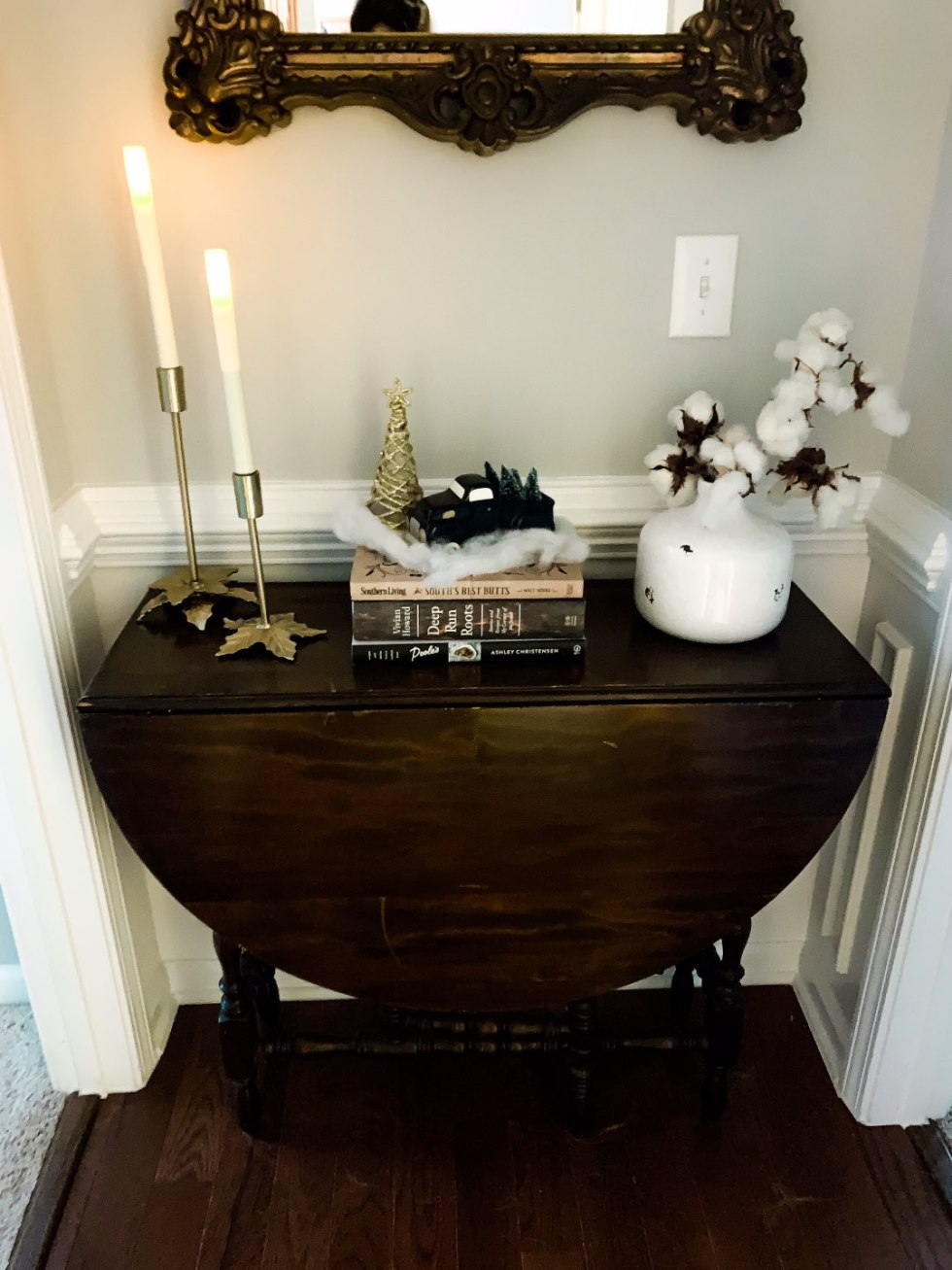 Holiday Home Decor Tour - I'm Fixin' To - @mbg0112 | Holiday Home Decor Tour by popular North Carolina life and style blog, I'm Fixin' To: image of a hallway table with taper candles, a gold Christmas tree, and a black pick up truck with mini Christmas tree in it.
