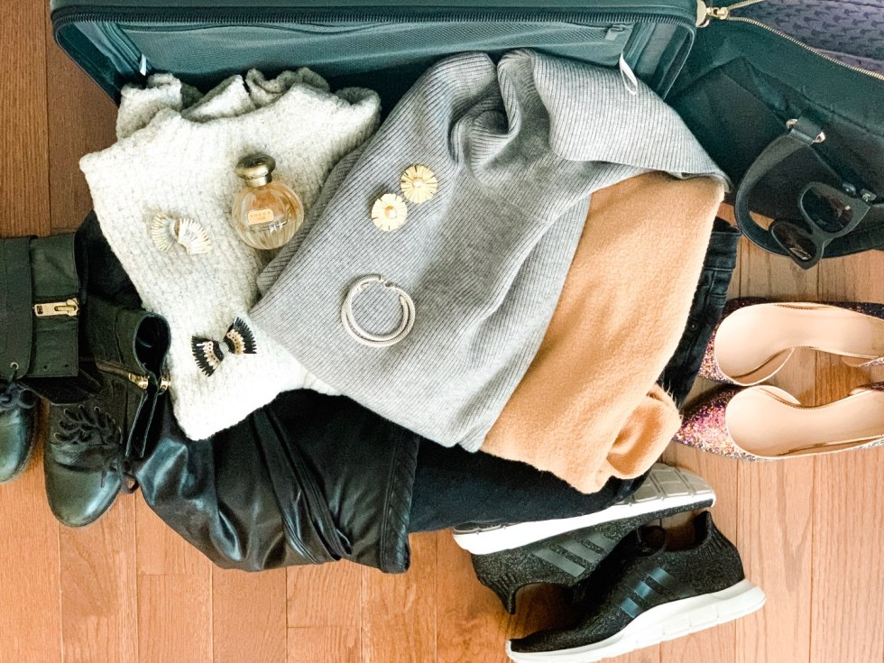 A Complete Winter Travel Packing List: all the Winter Essentials you Need - I'm Fixin' To - @mbg0112 | A Complete Winter Packing Essentials List by popular North Carolina travel blog, I'm Fixin To: image of a suitcase packed with sweaters, boots, point toe flats, Adidas sneakers, earrings, perfume and a jacket.