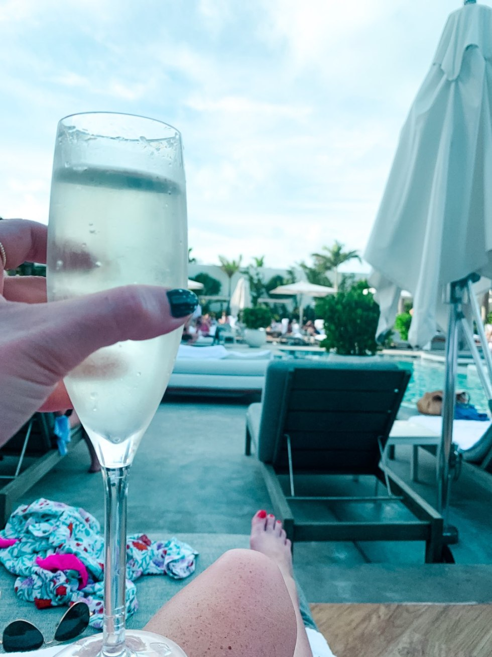 Warming Up in the Bahamas: the Best Things to Do at Baha Mar - I'm Fixin' To - @mbg0112 | Warming Up in the Bahamas: the Best Things to Do in Baha Mar by popular North Carolina travel blog, I'm Fixin' To: image of woman sitting by a pool at the Baha Mar.