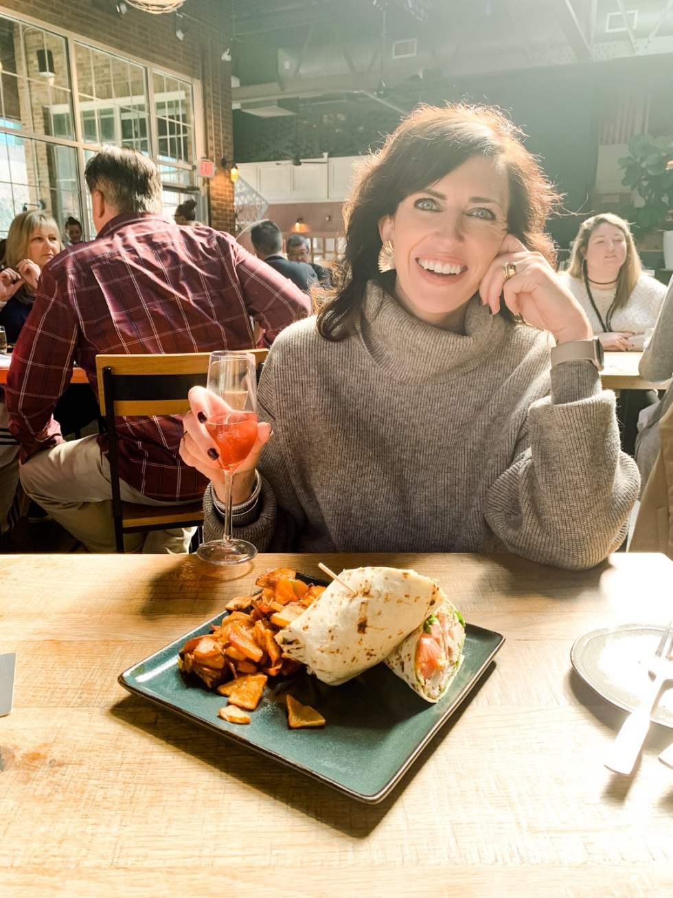 Where to Get Brunch in Raleigh: the 7 Best Spots - I'm Fixin' To - @mbg0112 | Brunch in Raleigh by popular Raleigh blog, I'm Fixin To: image of a woman eating at Whiskey Kitchen.