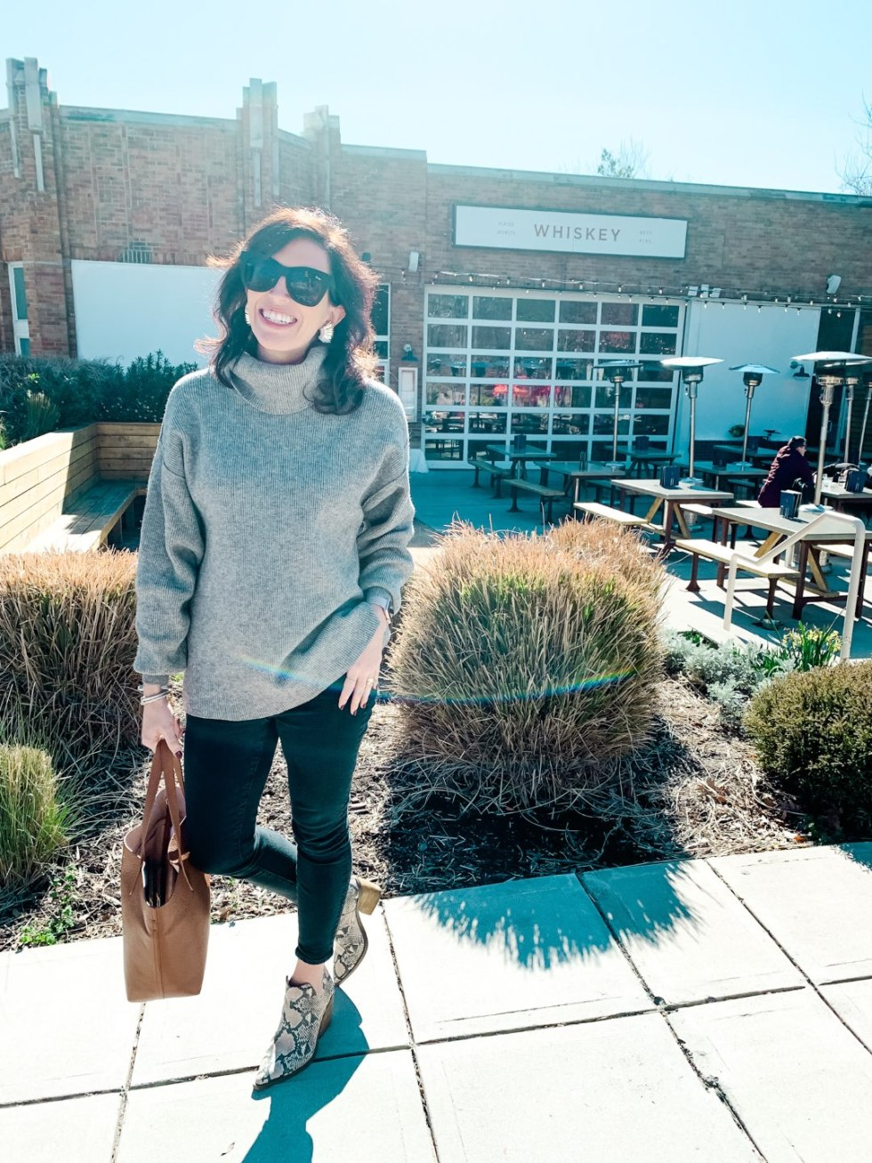 "Where to Get Brunch in Raleigh: the 7 Best Spots - I'm Fixin' To - @mbg0112 | Brunch in Raleigh by popular Raleigh blog, I'm Fixin To: image of a woman standing outside Whiskey Kitchen and wearing a Free People Softly Structured Knit Tunic, J. Crew 10"" highest-rise skinny jean in black denim, Nordstrom Gigietta Bootie VINCE CAMUTO, and Nordstrom After Hours 50mm Square Sunglasses QUAY AUSTRALIA."