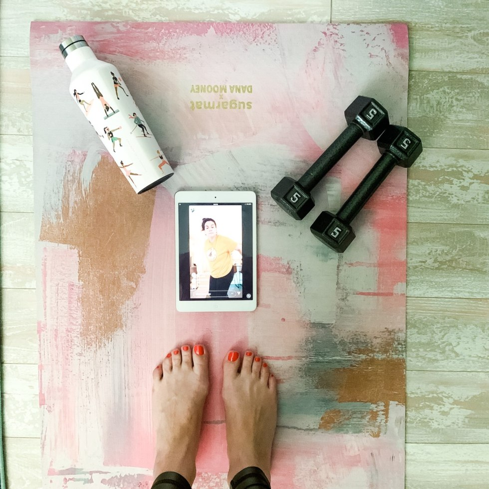 How to Stay Active at Home by popular NC lifestyle blog, I'm Fixin' To: image of a woman standing on a yoga mat that has a white metal water bottle, 5 lbs hand weights, and a ipad on it.