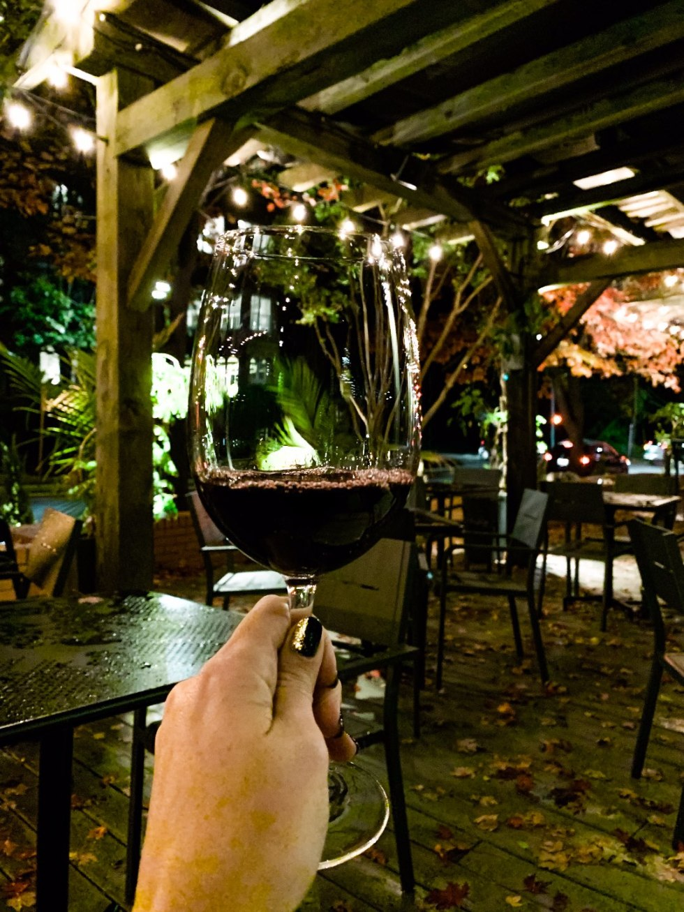 The 20 North Carolina Restaurants I Can't Wait to Visit after Quarantine - I'm Fixin' To - @mbg0112 | Best North Carolina Restaurants by popular N.C. blog, I'm Fixin' To: image of a woman holding a glass of wine at Wye Hill restaurant.