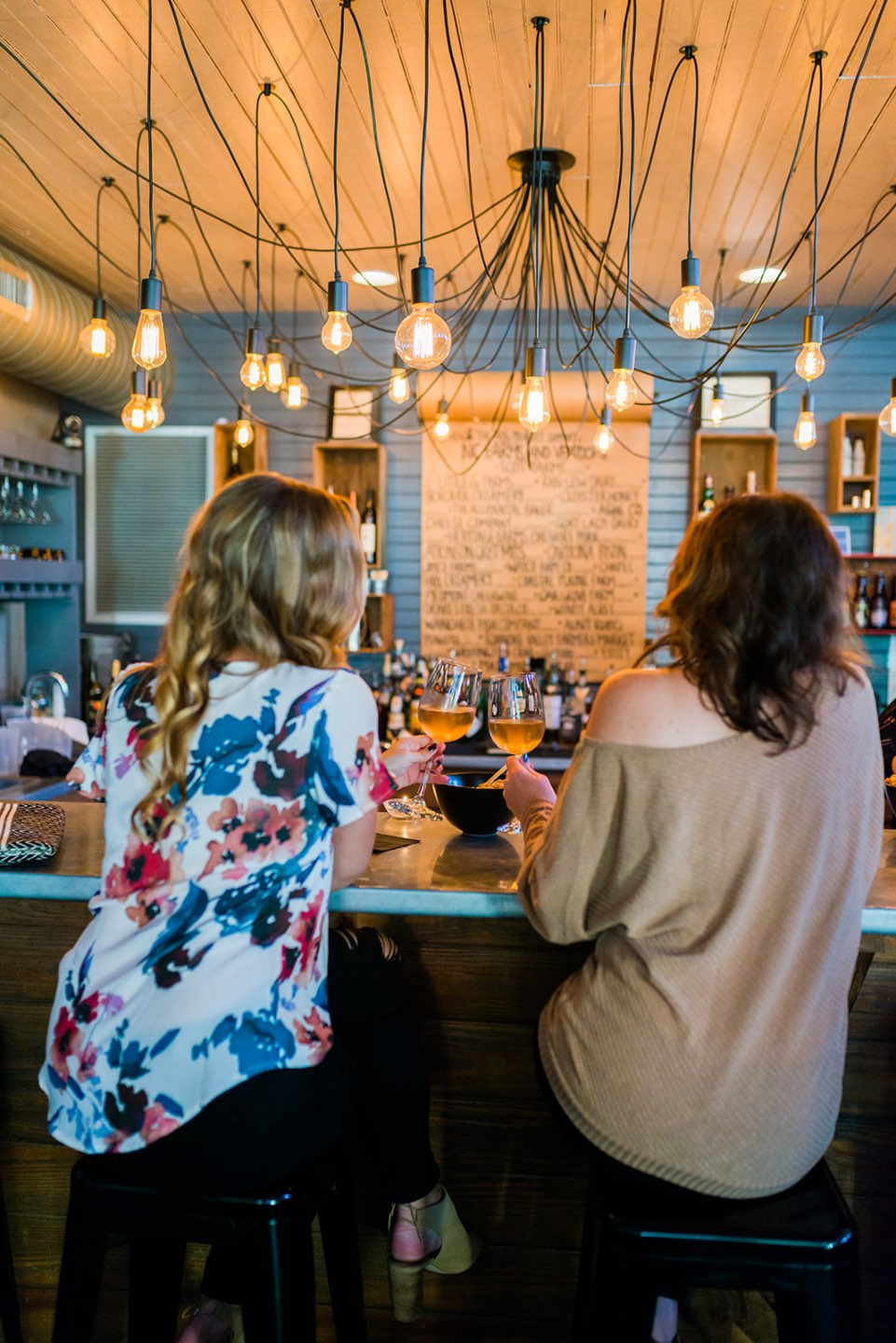The 20 North Carolina Restaurants I Can't Wait to Visit after Quarantine - I'm Fixin' To - @mbg0112 | Best North Carolina Restaurants by popular N.C. blog, I'm Fixin' To: image of two women sitting at the bar at the Hen and the Hog restaurant.