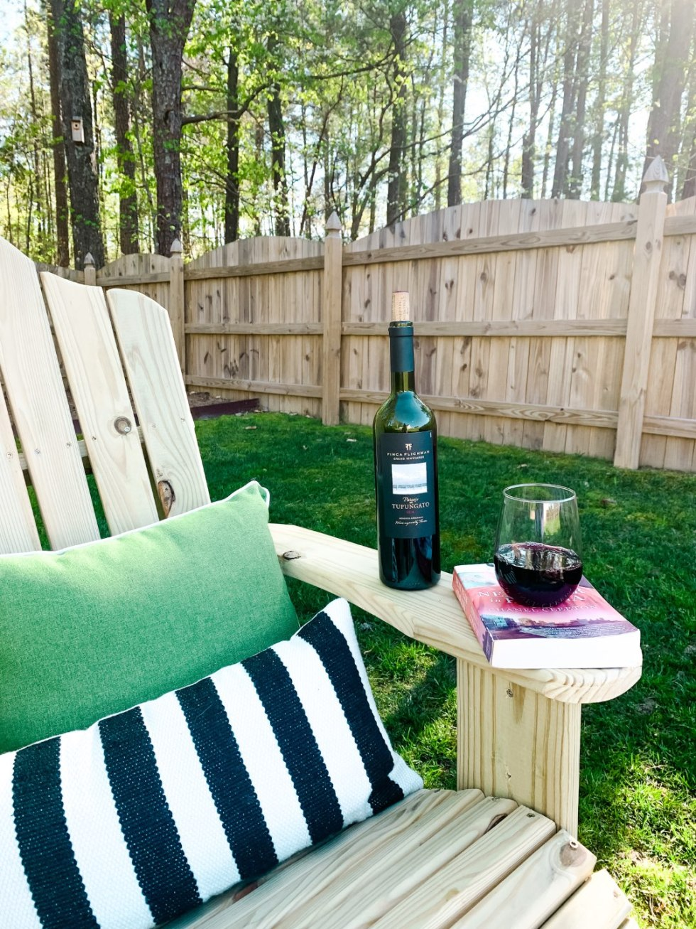 Top 10 Best Wines by popular N.C. lifestyle blog, I'm Fixin' To: image of a bottle of Finca Flinchman Malbec on a lounge chair outside.