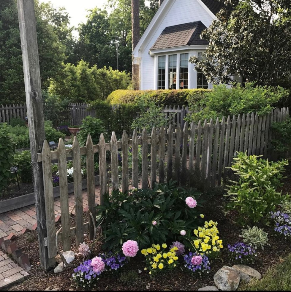 Mother's Day Gift Ideas for the Homebound Mom - I'm Fixin' To - @mbg0112 | Thoughtful Mother's Day Gift Ideas by popular N.C. lifestyle blog, I'm Fixin' To: image of a white house with a picket fence, brick paved walkway and flower garden.