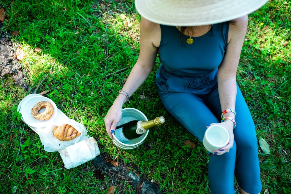 Picnic in Raleigh by popular North Carolina blog, I'm Fixin' To: image of a woman sitting on the grass next to a bottle of wine and a croissant and a bagel.