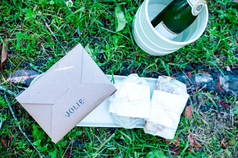 The Top 3 Places to Have a Picnic in Raleigh - I'm Fixin' To - @mbg0112 | Picnic in Raleigh by popular North Carolina blog, I'm Fixin' To: image of a bottle of wine and a Jolie to-go box on the grass.