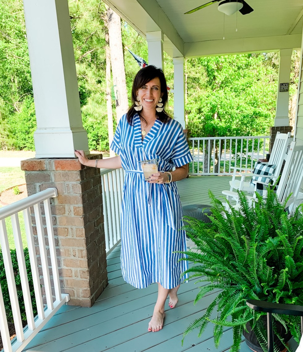 3 Happy Hour Gin Cocktails to Enjoy At Home - I'm Fixin' To - @mbg0112 | Happy Hour Cocktails by popular North Carolina lifestyle blog, I'm Fixin' To: image of a woman standing on her front porch while holding a gin cocktail and wearing a Hart JANUS PENDANT ON LONG LINK CHAIN, Michelle McDowell Tijuana Earrings, and J.Crew Cotton poplin maxi dress in awning stripe.
