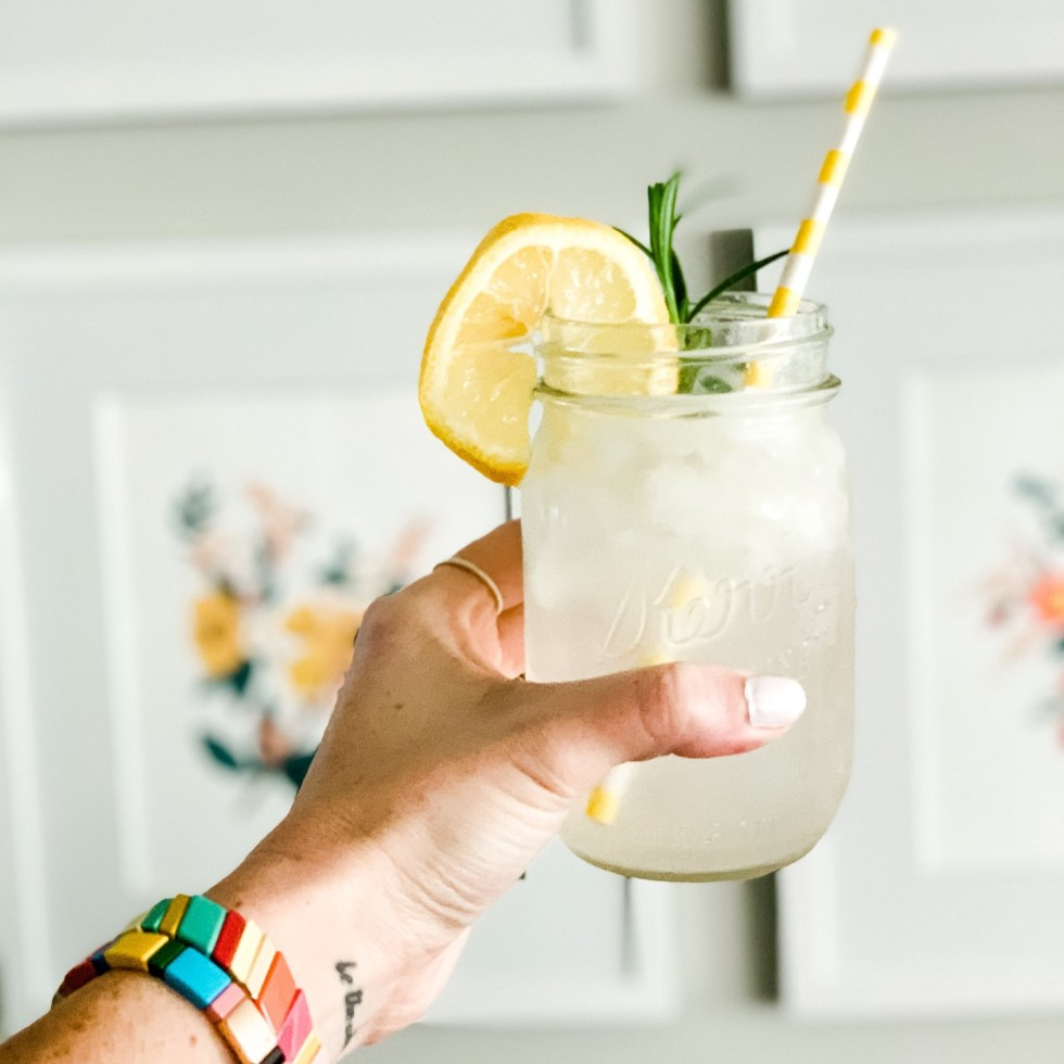 3 Happy Hour Gin Cocktails to Enjoy At Home - I'm Fixin' To - @mbg0112 | Happy Hour Cocktails by popular North Carolina lifestyle blog, I'm Fixin' To: image of a woman holding a gin cocktail in a mason jar.