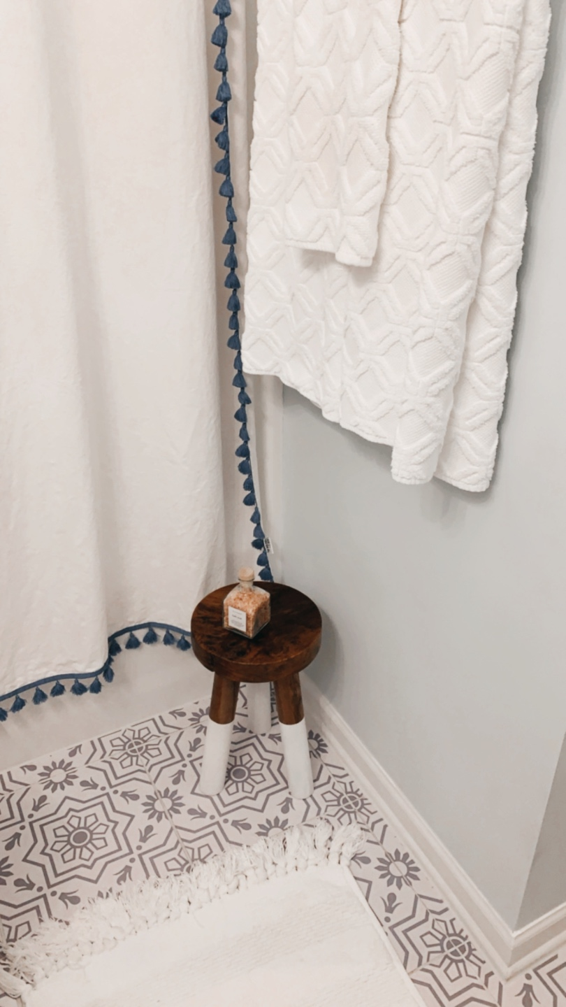 "How to Renovate a Guest Bathroom on a Budget: 5 Practical Tips - I'm Fixin' To - @mbg0112 | How to Update a Guest Bathroom on a Budget by popular North Carolina life and style blog: image of a guest bathroom decorated with Serena & Lily Hand Towels, Target 28"" Round Decorative Wall Mirror, Target 13"" Decorative Coiled Rope Square Base Tapered Basket, Etsy Snazzy Decal tile sticker, Serena and Lily shower curtain, a white bath mat, dipped stool, and Wayfair Nunes 3-Light Dimmable Antique Brass Vanity Light."