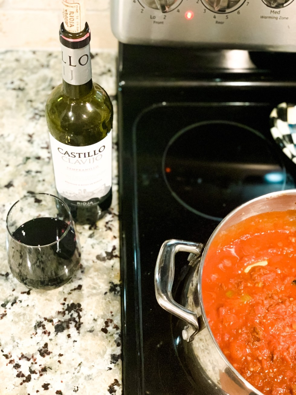 7 Recipes I Have Tried During Quarantine - I'm Fixin' To - @mbg0112 | Easy Recipes for Two by popular North Carolina lifestyle blog, I'm Fixin' To: image of a bottle of red wine rest next to a pot of red meat sauce.