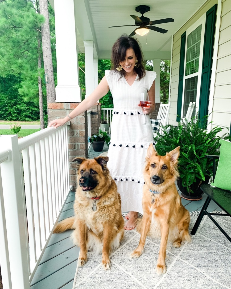 2020 Summer Wardrobe Capsule: 25 Pieces your Closet Needs - I'm Fixin' To - @mbg0112 | Summer Wardrobe Capsule by popular North Carolina fashion blog, I'm Fixin' To: image of a woman standing on her front porch with her two dogs and wearing a white tiered tassel dress and gold statement earrings.