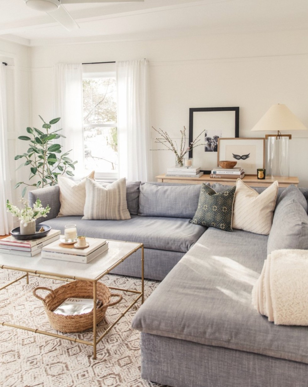 Inspiration Board: Living Room - I'm Fixin' To - @mbg0112 | Living Room Inspiration by popular N.C. life and style blog, I'm Fixin' To: image of a living room with a white and brown area rug, white and gold bamboo coffee table, and a blue sectional couch.