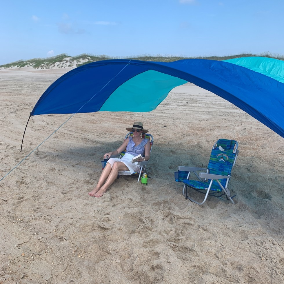 Travel Tips for Staying Safe & Healthy in Quarantine - I'm Fixin' To - @mbg0112 | Travel Tips for Staying Safe & Healthy by popular North Carolina travel blog, I'm Fixin' To: image of a woman sitting under a sunshade on the beach.