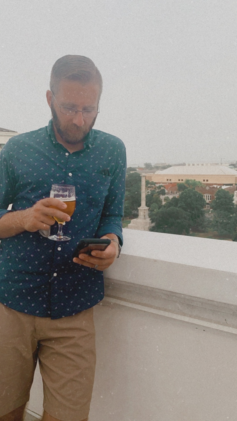Travel Tips for Staying Safe & Healthy by popular North Carolina travel blog, I'm Fixin' To: image of a man standing outside and holding a glass of beer while looking at his smartphone.