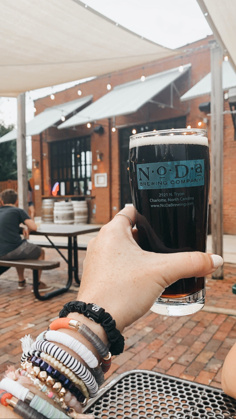 Weekend in Charlotte: Best Breweries and Places to Eat - I'm Fixin' To - @mbg0112 | Weekend in Charlotte by popular N.C. travel blog, I'm Fixin' To: image of a woman holding a glass of beer at NoDa Brewing Company.