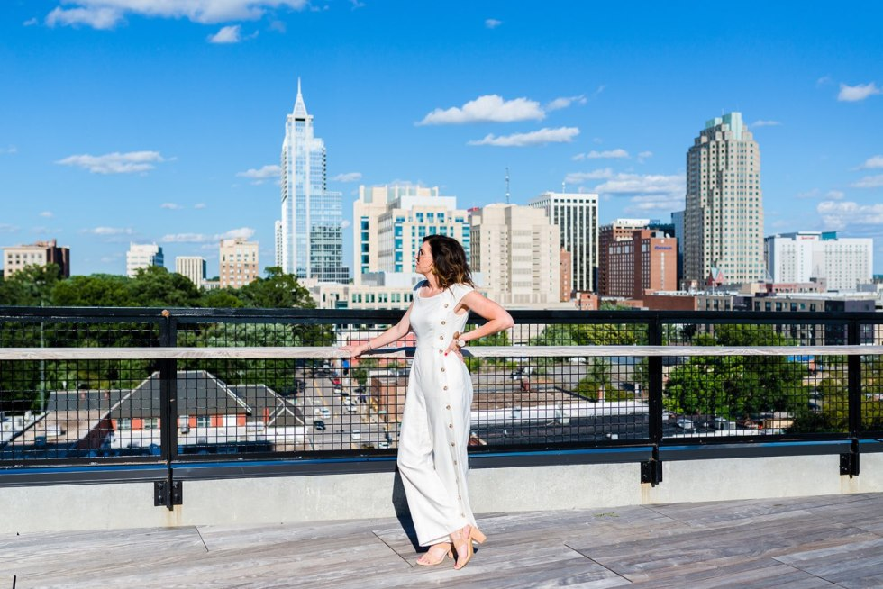 Local Love: 10 Best Places to Photograph in North Carolina - I'm Fixin' To - @mbg0112 | Best Places to Photography in North Carolina by popular N.C. lifestyle blog, I'm Fixin' To: image of a woman wearing a white jumpsuit and standing on The Rooftop at the Dillon in Raleigh, N.C.