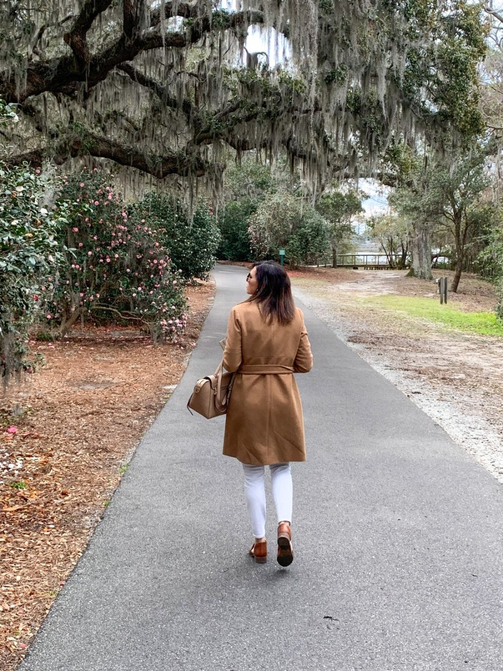 Best Places to Photography in North Carolina by popular N.C. lifestyle blog, I'm Fixin' To: image of a woman walking on a asphalt pathway under a tree covered in Spanish Moss at the Airlie Gardens.
