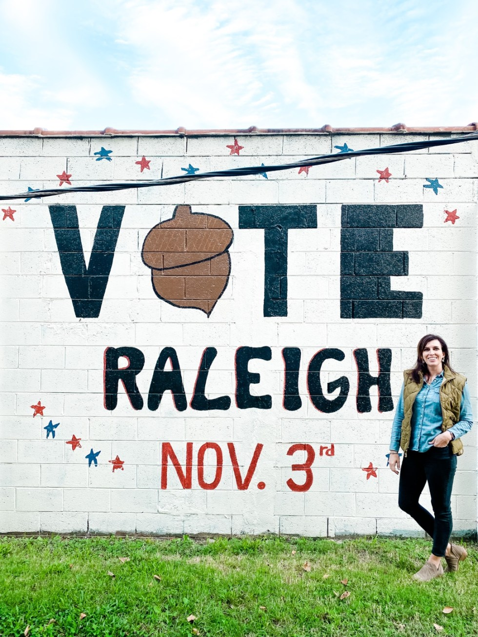 Civic Engagement Fashion Top Picks for Women - I'm Fixin' To - @mbg0112 | Civic Engagement by popular N.C. fashion blog, I'm Fixin' To: image of a woman wearing a denim shirt, green puffer vest, black jeans, and brown ankle boots and standing in front of a 'Vote Raleigh' wall mural.