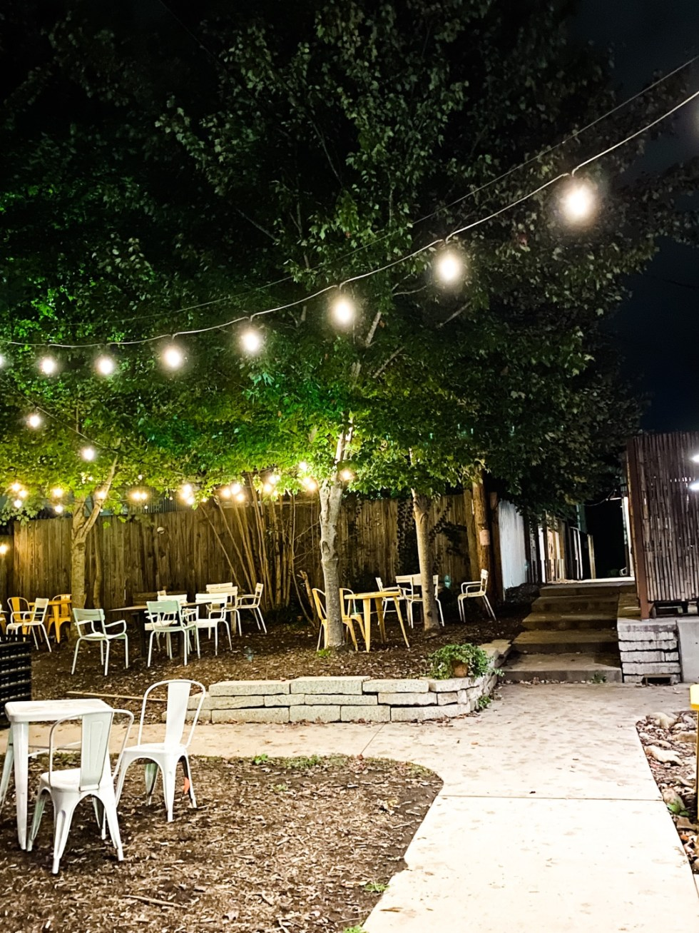 A Casual Weekend in Asheville: the Best Things to Do with your Dogs - I'm Fixin' To - @mbg0112   Weekend In Asheville by popular NC travel blog, I'm Fixin' To: image of a patio with tables, chairs, and bistro lights.