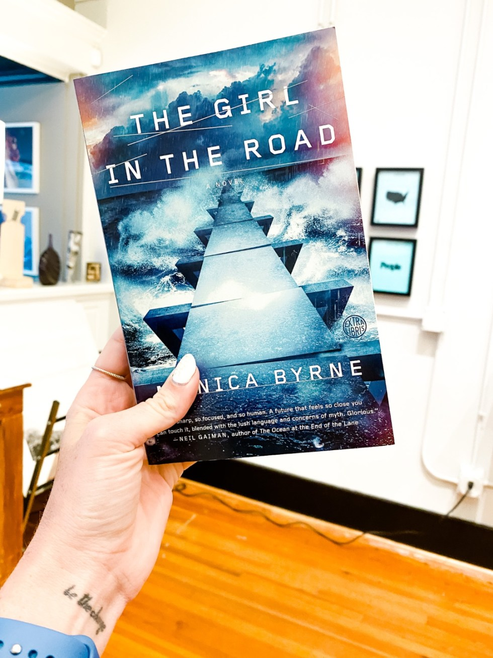 "Date Night at the The Streetery in Downtown Durham - I'm Fixin' To - @mbg0112 |The Streetery in Downtown Durham by popular N.C. blog, I'm Fixin' To: image of a woman holding the book ""The Girl In The Road"" in the PS118 gallery and event space."