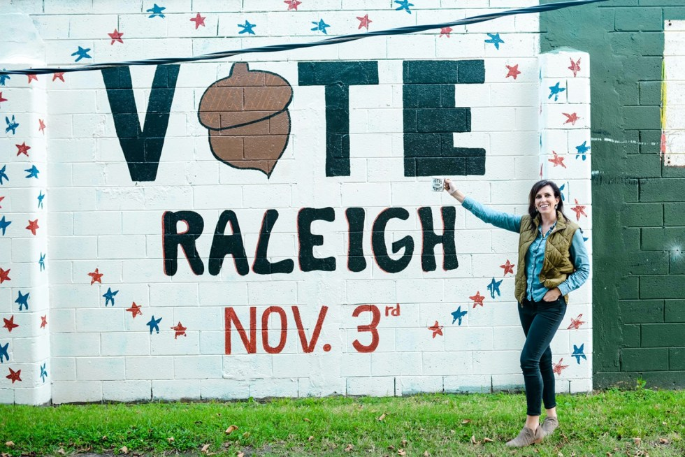 "Summer to Fall Fashion: 3 Transitional Fall Outfits for the Southern Heat - I'm Fixin' To - @mbg0112 | Summer to Fall fashion by popular NC fashion blog, I'm Fixin' To: image of a woman standing in front of a Vote Raleigh wall mural and wearing a J. Crew puffer vest, J. Crew 8"" stretchy toothpick jean in true black, Nordstrom Arendara Bootie VINCE CAMUTO, and holding a Wayfair White You Go Girl Votes for Women Coffee Mug."
