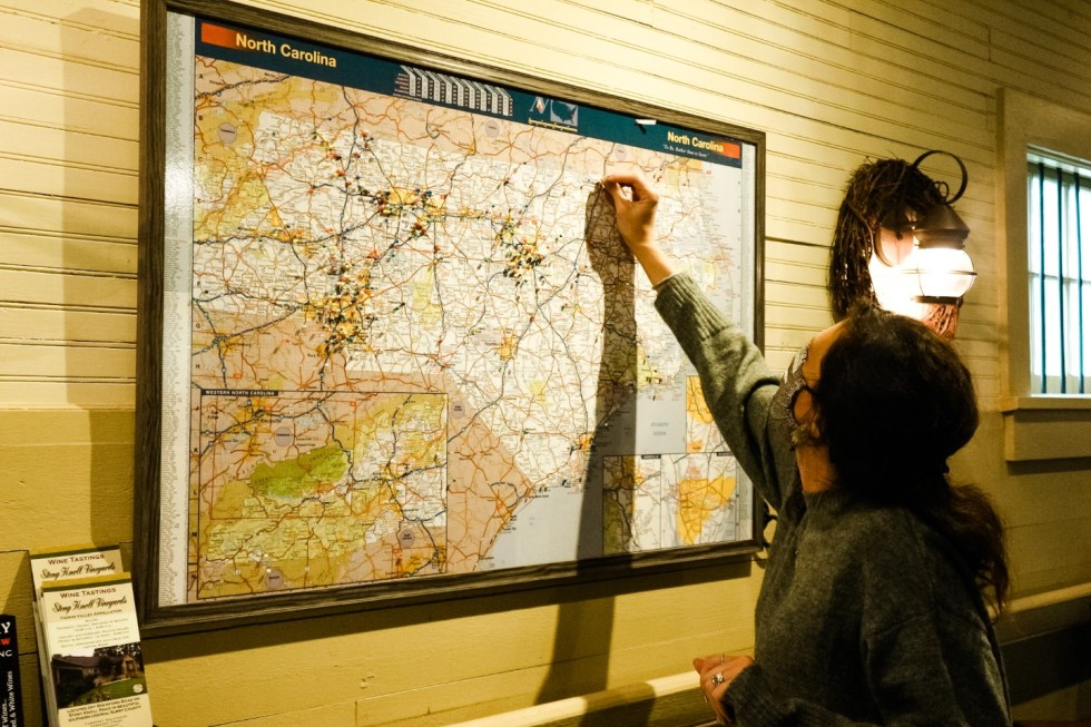 Western NC Wineries: 6 Wineries to Visit During your Next Girls' Weekend - I'm Fixin' To - @mbg0112 |Western NC Wineries by popular NC blog, I'm Fixin' To: image of a woman putting a pin in a North Carolina map.