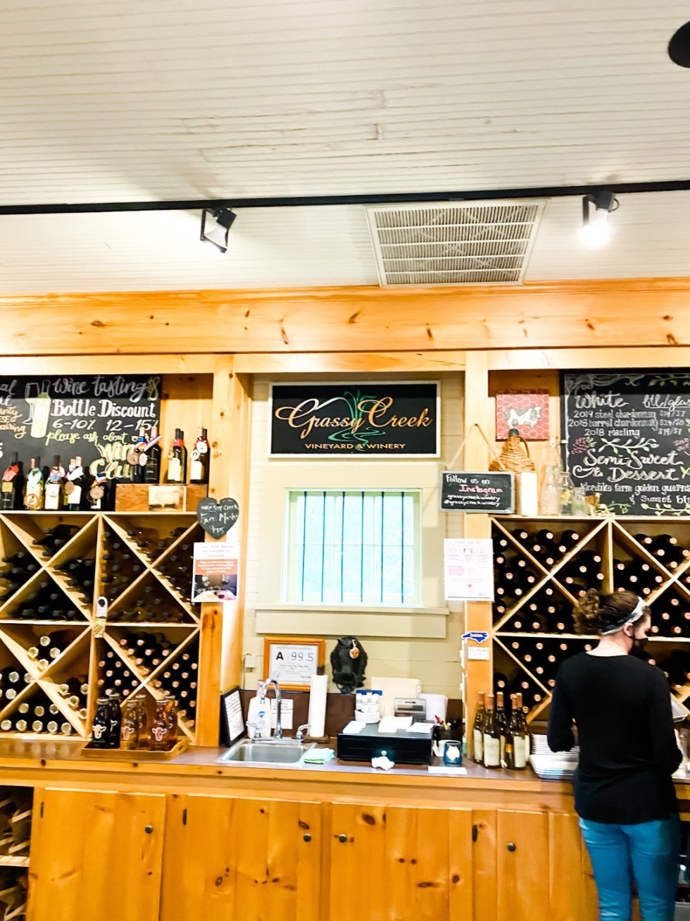 Western NC Wineries: 6 Wineries to Visit During your Next Girls' Weekend - I'm Fixin' To - @mbg0112 |Western NC Wineries by popular NC blog, I'm Fixin' To: image of wine displays at Grassy Creek vineyard and winery.