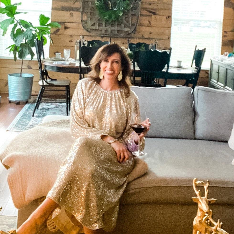 List of Positive Things by popular NC lifestyle blog, I'm Fixin' To: image of a woman wearing a sequin maxi dress and sitting on her grey sectional couch while holding a glass of red wine.