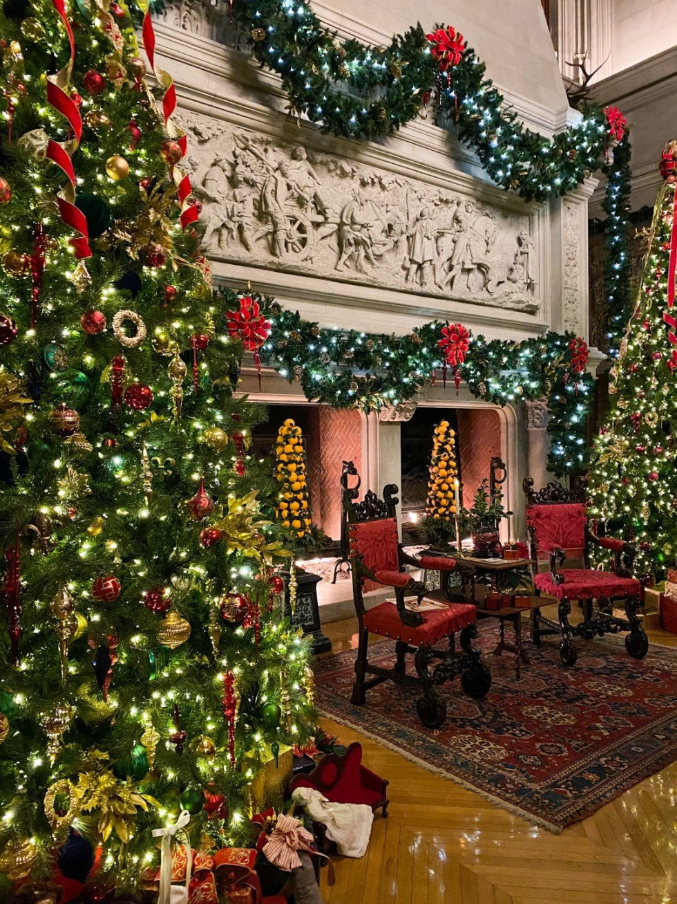 Christmas in Asheville: a Weekend Getaway During the Holidays - I'm Fixin' To - @imfixintoblog |Christmas in Asheville NC by popular NC lifestyle blog, I'm Fixin' To: image of two large Christmas trees next to a first place decorated with garland at the Biltmore house.