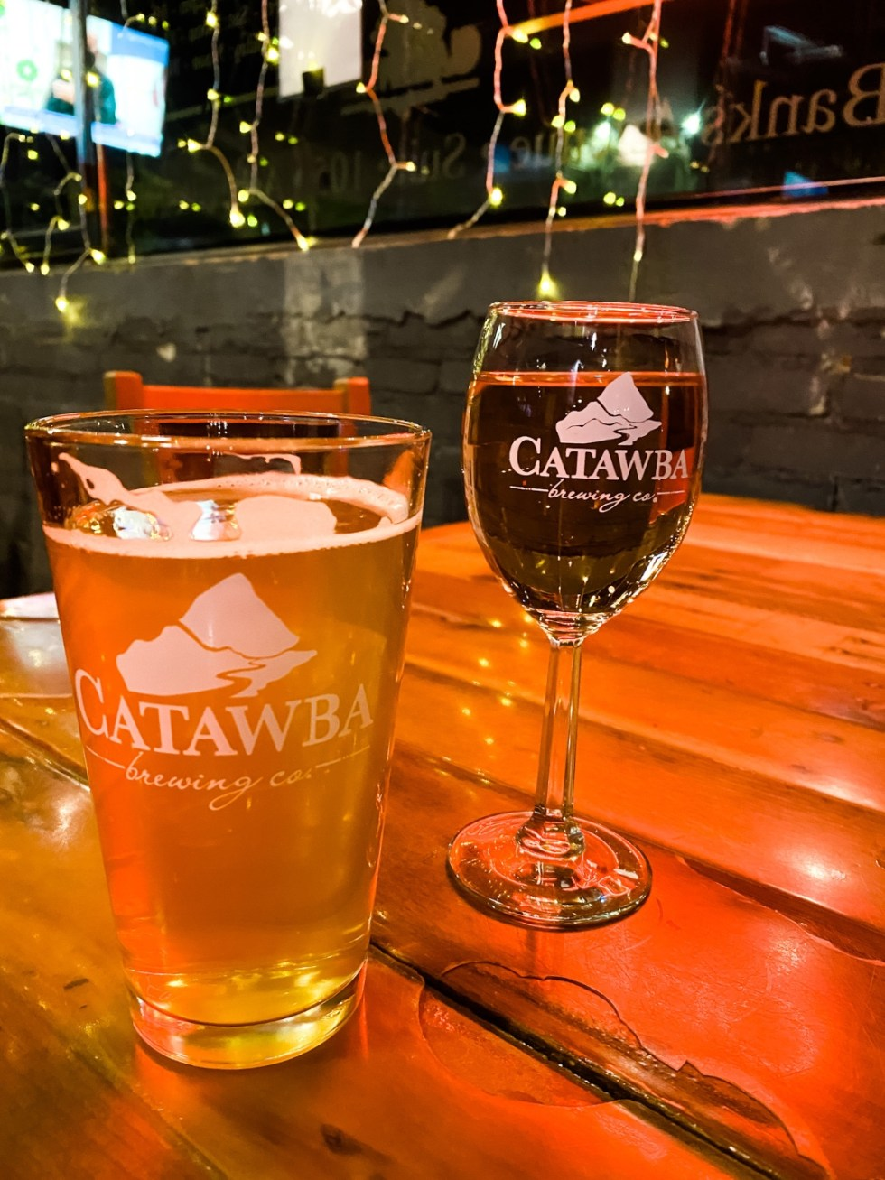 Christmas in Asheville: a Weekend Getaway During the Holidays - I'm Fixin' To - @imfixintoblog |Christmas in Asheville NC by popular NC lifestyle blog, I'm Fixin' To: image of a glass of beer and a glass of wine at Catabaw Brewing Company.