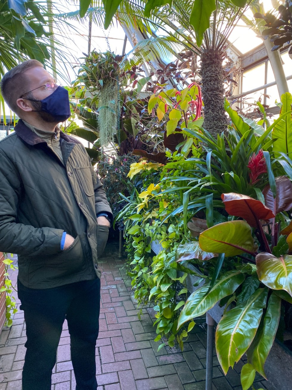 Christmas in Asheville: a Weekend Getaway During the Holidays - I'm Fixin' To - @imfixintoblog |Christmas in Asheville NC by popular NC lifestyle blog, I'm Fixin' To: image of a man walking through a greenhouse and looking at exotic plants.