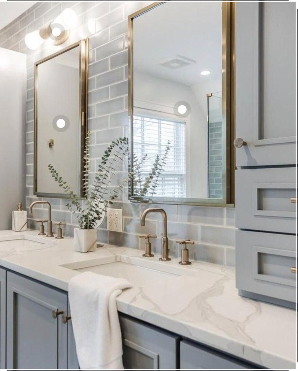 Most Popular Posts by popular NC lifestyle blog, I'm Fixin' To: image of a bathroom with a grey vanity, double sinks, gold framed rectangular mirrors, and gold faucets.