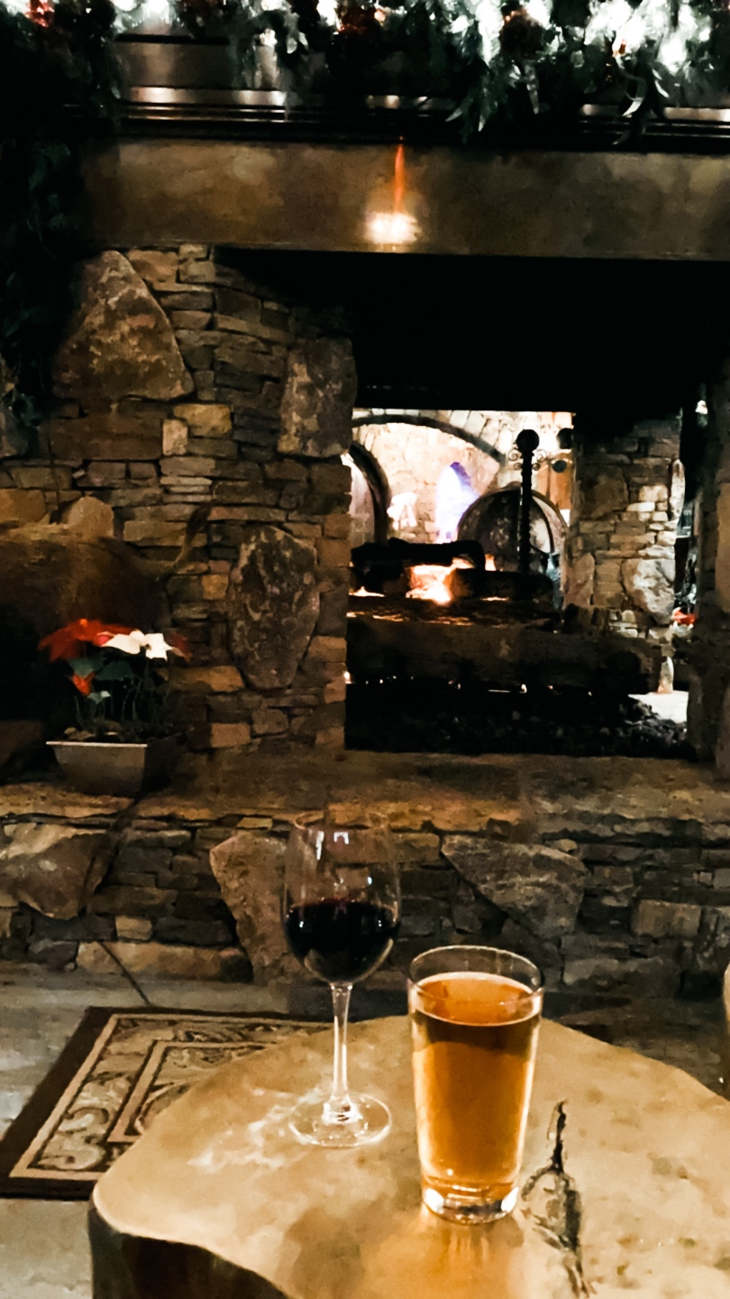 New Year Goals by popular NC lifestyle blog, I'm Fixin' To: image of a glass of wine and a glass of beer on a log stump table in front of a stone fireplace.