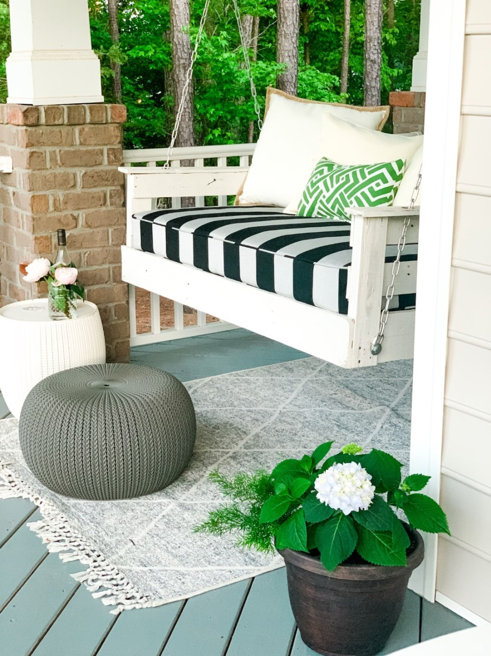 3 Years in Our Ranch: Home Updates - I'm Fixin' To - @imfixintoblog |Home Updates by popular NC life and style blog, I'm Fixin' To: image of a front porch decorated with a white porch swing, grey and white rug, potted plant, and grey ottoman.
