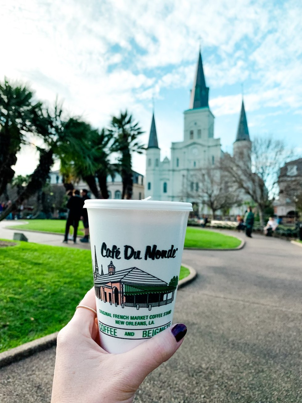 2020, a Year in Review: our Travel Adventures - I'm Fixin' To - @imfixintoblog |Year in Review by popular NC travel blog, I'm Fixin' To: image of a woman holding a Cafe Du Monde cup in New Orleans.