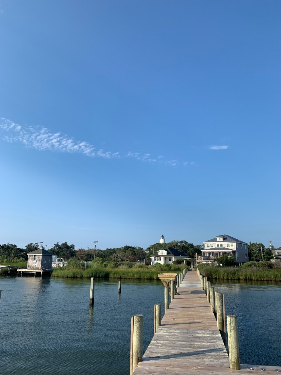 2020, a Year in Review: our Travel Adventures - I'm Fixin' To - @imfixintoblog |Year in Review by popular NC travel blog, I'm Fixin' To: image of a pier leading to some white buildings in Ocracoke.