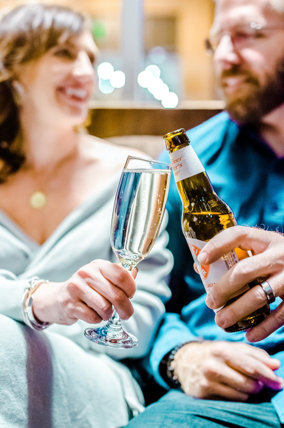 Valentine's Date Night Ideas by popular NC lifestyle blog, I'm Fixin' To: image of a husband and wife sitting together and clinking a wine glass and beer bottle together.