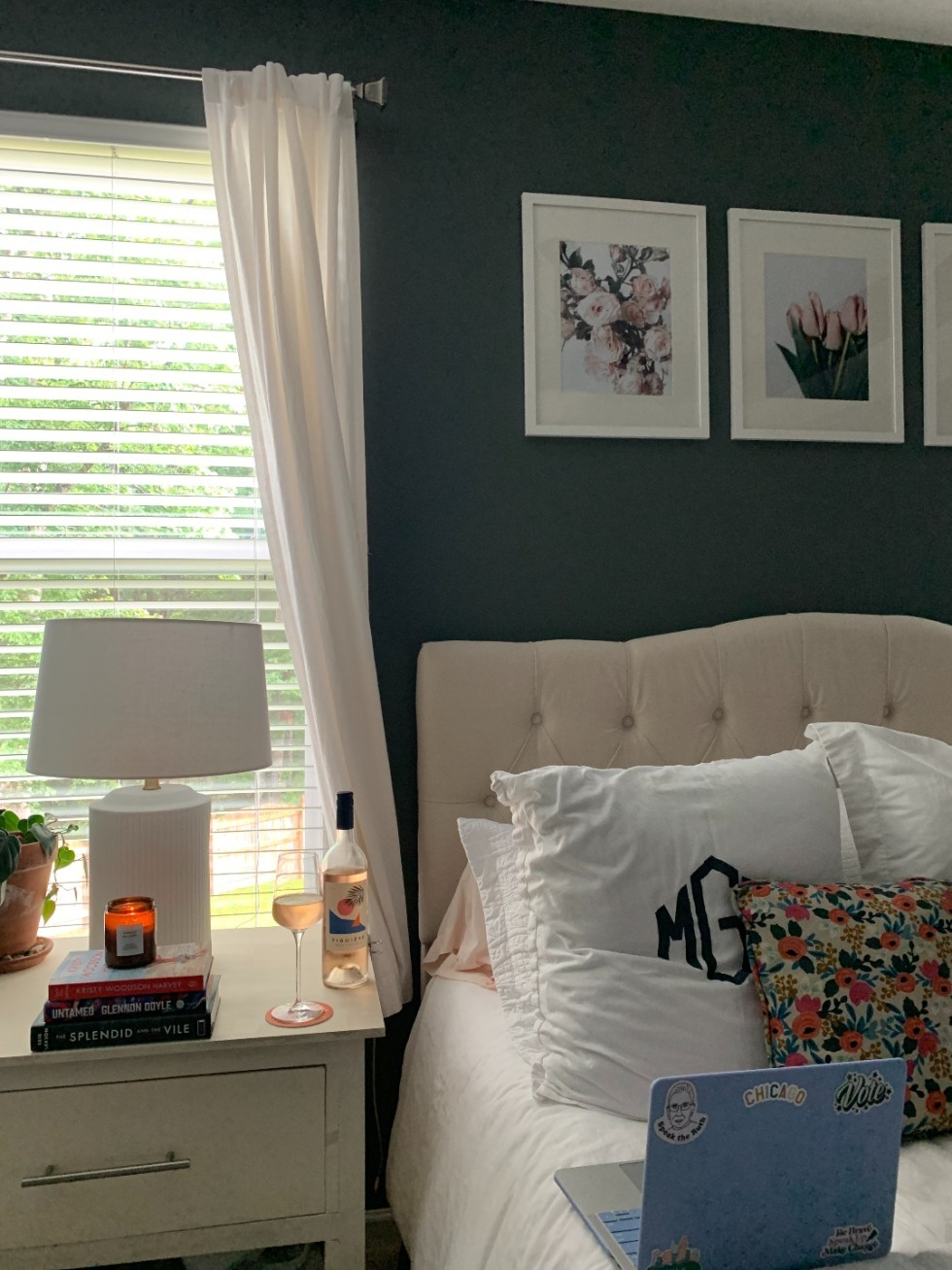 How to Make your Home Cozy: 10 Easy Ways - I'm Fixin' To - @imfixintoblog |How to Make Your Home Cozy by popular NC life and style blog, I'm Fixin' To: image of a bedroom with a bed with a white tuft headboard ad white bedding, floral print artwork, white night stands, white curtains, grey walls, and a serving tray set with a vase of flowers and a candle.