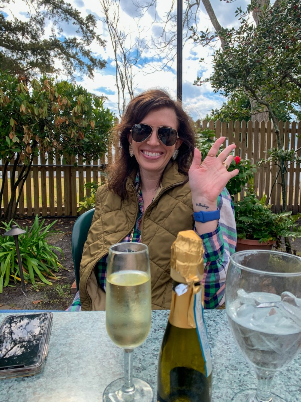 Weekend Travel: The Best Things to Do in Beaufort NC in 48 Hours - I'm Fixin' To - @imfixintoblog |Things to Do in Beaufort NC by popular NC travel blog, I'm Fixin' To: image of a woman sitting at an outdoor table set with a bottle of white wine.