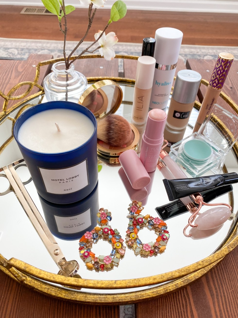 Best Makeup Products by popular NC beauty blog, I'm Fixin' To: image of various beauty products, floral statement drop earrings, and a Hotel Lobby candle on a mirrored gold tray.