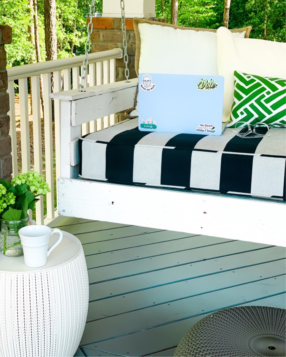 Women in the Triangle by popular NC lifestyle blog, I'm Fixin' To: image of a porch swing with a black and white stripe seating cushion and white and green throw pillows and a light blue laptop resting on it.