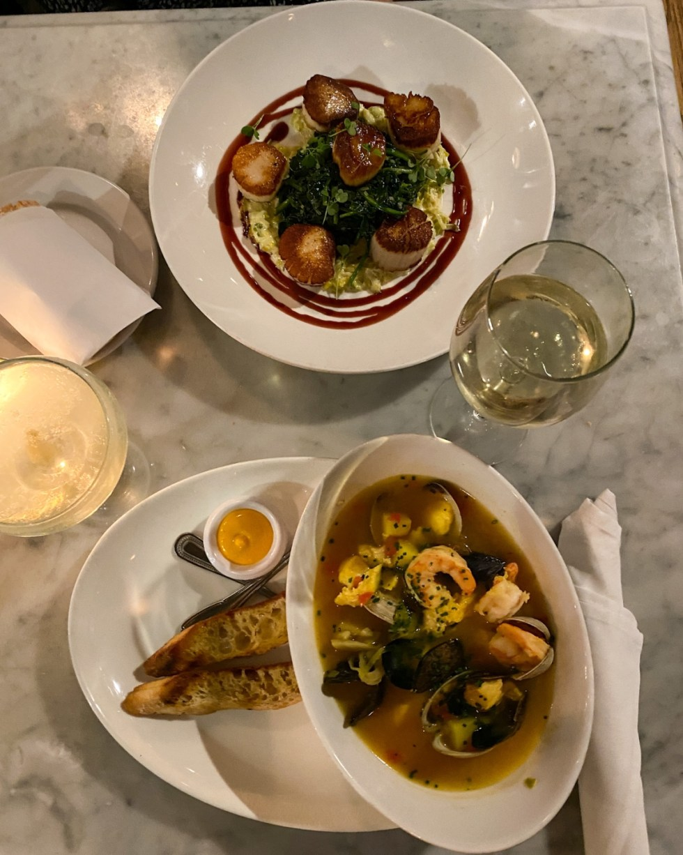 A Spring Weekend in Wilmington, NC: the Best Things to Do - I'm Fixin' To - @imfixintoblog |Weekend in Wilmington by popular NC travel blog, I'm Fixin' To: image of a plate of scallops, glass filled with white wine, and a bowl of seafood soup.